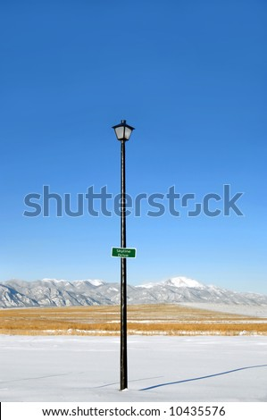 "Lamp post has street sign that reads ""skyline drive.""  Height of pole and Pike's Peak of the Colorado Rocky Mountains in background make for a very apt street name ""skyline."""