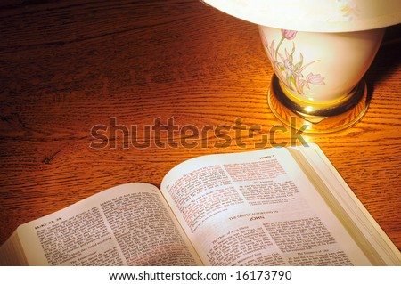 Lamp shining on a Bible, metaphor for the Bible's light to the world - stock photo