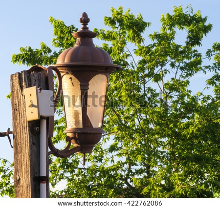 lamp with broken glass with a tree background - stock photo