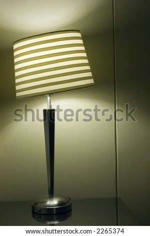 Lamp with skewed shade on night table in hotel room