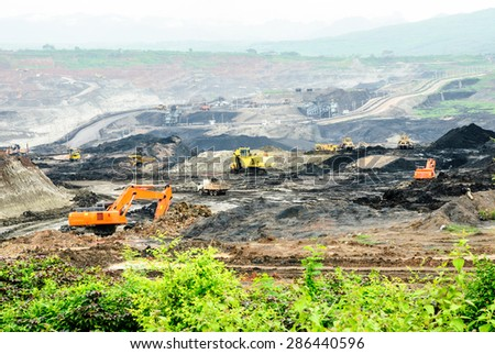 LAMPANG, THAILAND - AUG 24: The backhoes and the bulldozers excavate lignite in the coal mine on 24 August, 2013 at Mae Moh mine, Lampang, Thailand. - stock photo