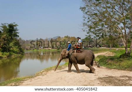 LAMPANG, THAILAND - FEB 18: Tourists riding an indian elephant during bathing in lake at Thai Elephant Conservation Center on February 18 2016. The Center - TECC, founded in 1993 under Royal Patronage