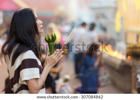 LAMPHUN, THAILAND, DECEMBER 31, 2014: A woman holding burning incense sticks and flowers is praying for the new year outside the Buddhist temple of Wat Phra That Hariphunchai in Lamphun, Thailand - stock photo