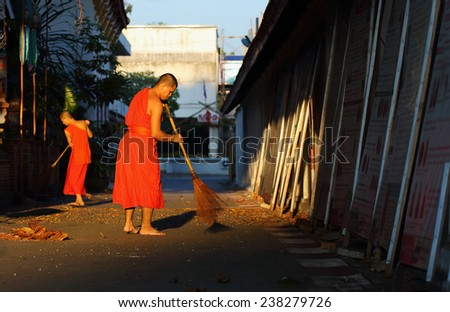 Lamphun, Thailand - November 11:Unidentified Buddhist monk was street sweeping in the morning at Wat Phra That Hariphunchai, Thailand temple in Lamphun, Thailand on November 11, 2014 - stock photo