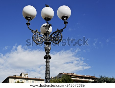 Lamppost with a beautiful iron pole and four globes on a public park in Florence, Italy - stock photo