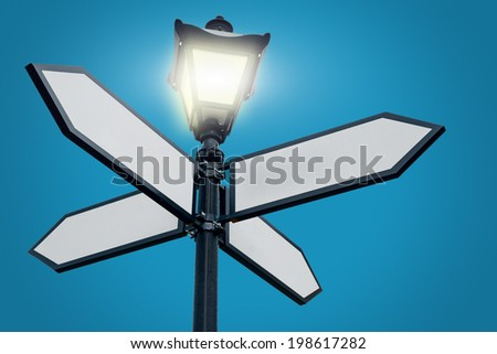 Lamppost with directional arrows - stock photo