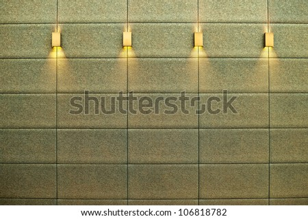 lamps illuminating the wall of a modern building listed