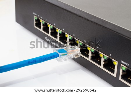LAN network switch with ethernet cables plugging in on white - stock photo