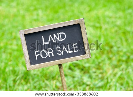 Land for sale - chalkboard with text on green grass background - stock photo
