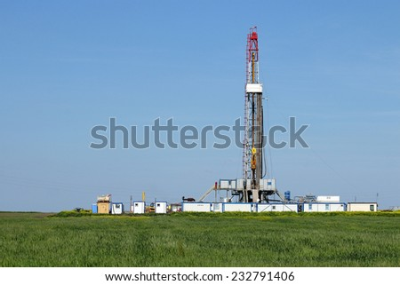 land oil drilling rig on green field - stock photo
