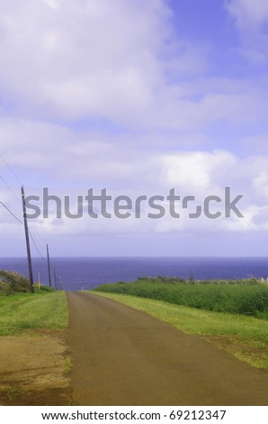 Land, sea, and sky: One-lane dirt road to the ocean - stock photo
