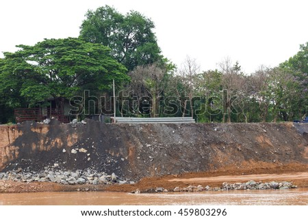 Land slide alongside the river erosion, which has the stones to ashes with concrete construction. - stock photo