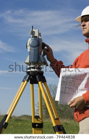 Land Surveyor in the field with theodolite on the tripod. - stock photo
