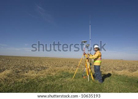 Land surveyor working with GPS unit. - stock photo