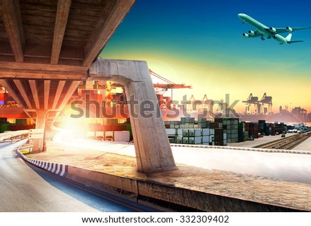 land transport run into shipping port and container dock with freight cargo plane flying above - stock photo