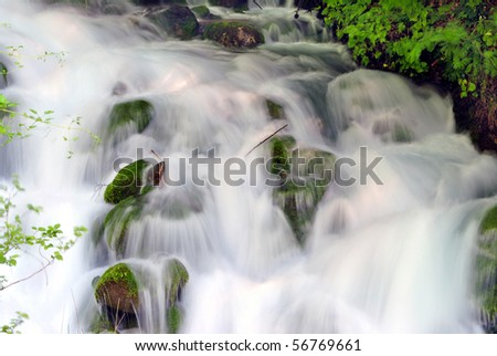 land which is fresh water with a waterfall and rushing noise coming from the Alps - stock photo