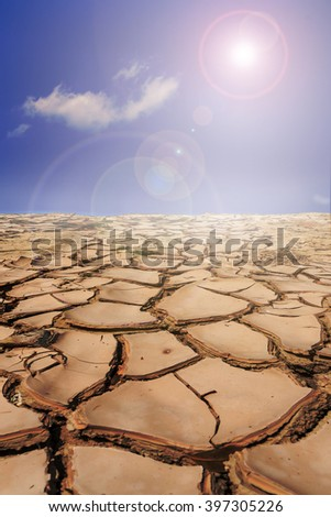 Land with dry cracked ground in sunny day - stock photo