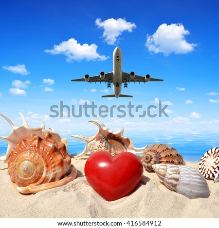 Landing an aircraft on a tropical island. In the foreground, shells with heart in sand. - stock photo