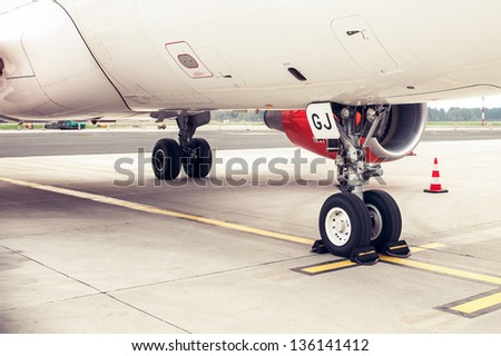 Landing gear and undercarriage of a jet airplane parked - stock photo
