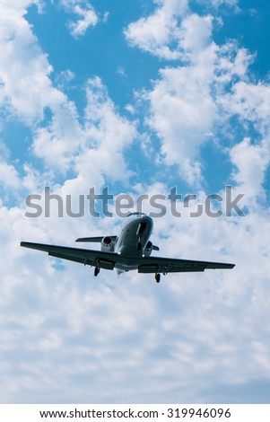 Landing jet plane with blue sky - stock photo