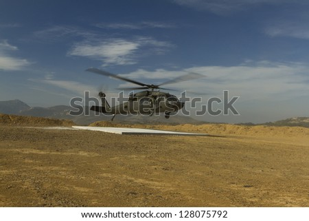 Landing military helicopter - stock photo