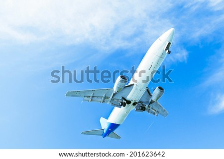 Landing plane on blue sky. Descending jet with landing gear. The view from below - stock photo