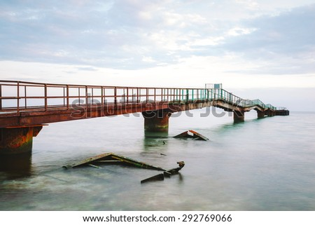 landscape abandoned old rusty pier in the morning - stock photo
