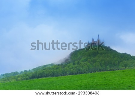 Landscape and Hohenzollern castle in haze during summer time in Germany - stock photo