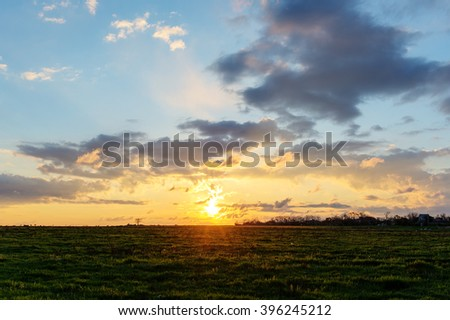 landscape at sunrise with sun and clouds - stock photo