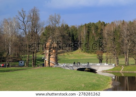 landscape: forest, river, tower of red brick, bridge - stock photo