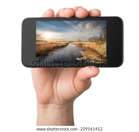 Landscape in a phone in hands isolated on white - stock photo
