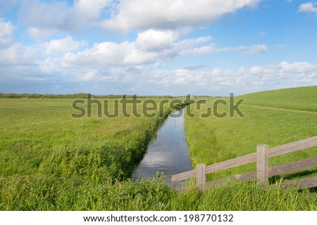 Landscape in Holland with dike and meadows at wadden island Tersschelling - stock photo