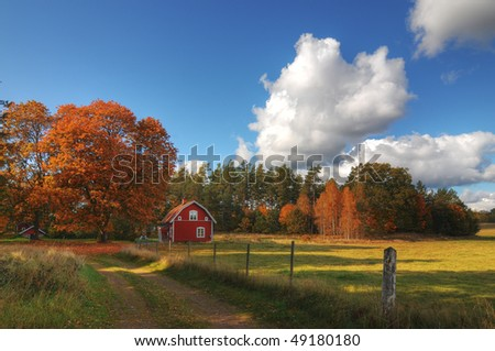 Landscape in Sweden in autumn with typical red wooden house. - stock photo