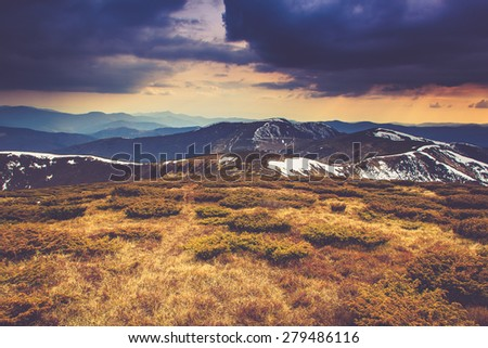 Landscape in the mountain:snowy tops and spring valleys. Dramatic overcast sky. Filtered image:cross processed vintage effect. - stock photo