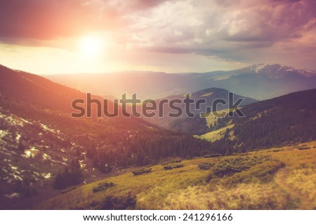 Landscape in the mountain:snowy tops and spring valleys.Fantastic evening glowing by sunlight. Filtered image:cross processed vintage effect. - stock photo