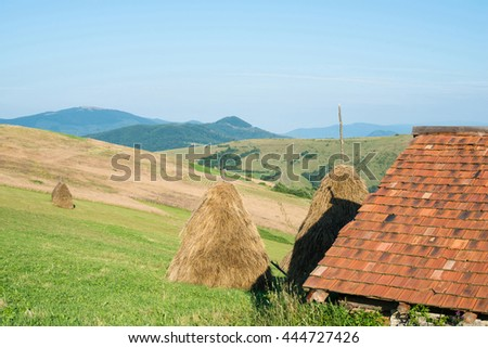Landscape in the Ukrainian Carpathian Mountains. Wooden house with orange tiled roof in the foreground,