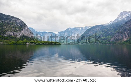 Landscape. Lakeside and snowy mountains at the cloudy day. Panorama.