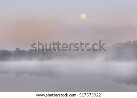 Landscape near sunrise of West Lake in fog and full moon, Michigan, USA