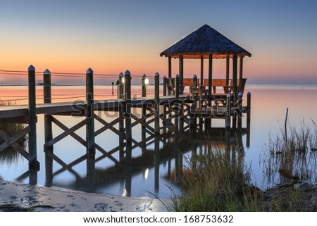 Landscape of a gazebo over Pamlico Sound in Cape Hatteras, North Carolina in the twilight hour on a very calm night. - stock photo