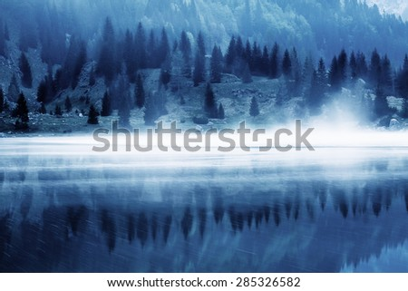 Landscape of a glacial lake. Misty fog over the surface. Blue tone. - stock photo