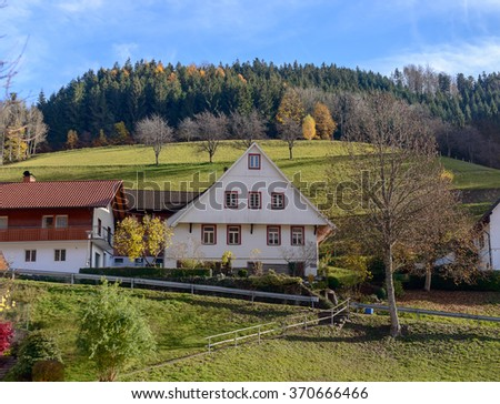 Landscape of autumn countryside with wooden farmhouses on green hill and rugged mountains in the background ~ Idyllic view of village at the foothill of rocky mountains on a sunny day - stock photo