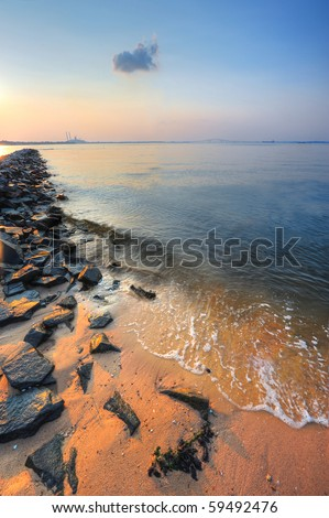 Landscape of Chesapeake bay beach and jetty at sunset with factory and Key bridge in background - stock photo