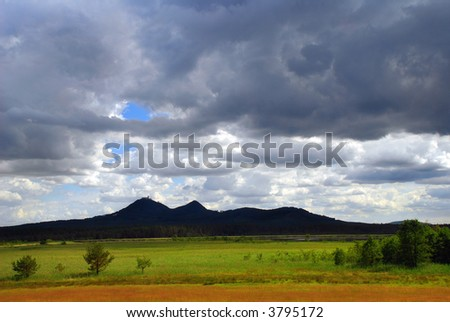 Landscape of czech countryside - Hills with medieval ruins of Bezdez castle under dramatic sky