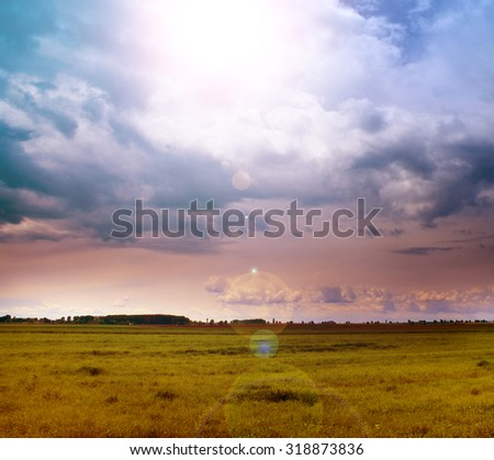 Landscape of green field and sun in the cloudy sky - stock photo
