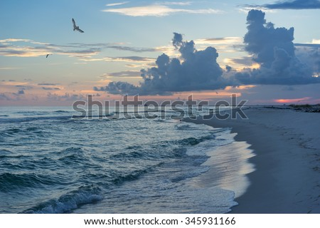 Landscape of incoming tide at a Gulf of Mexico beach in tones of saturated blue and teal with pink sunset and puffy dark cumulus clouds.