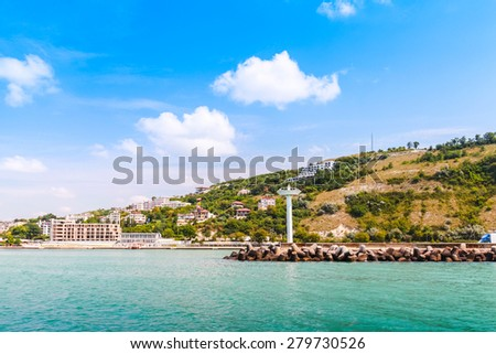 Landscape of Kavarna, coastal town and seaside resort in northeastern Bulgaria, Black Sea coast. Entrance to the port with white lighthouse tower - stock photo