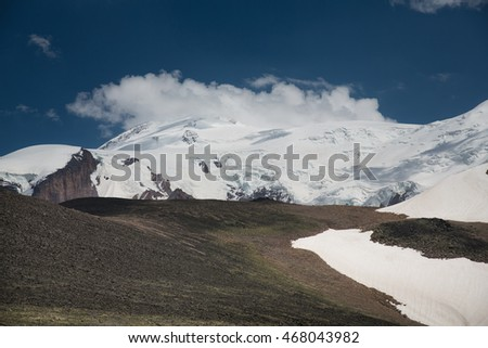 landscape of mountains, clouds, fog, green grass, snow, lake