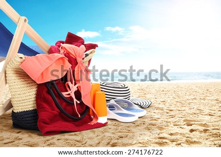 landscape of ocean and beach with shoes red towel and swimwear