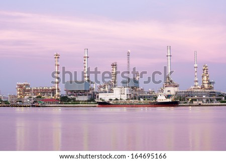 landscape of Oil refinery plant along river with tanker at dusk - stock photo