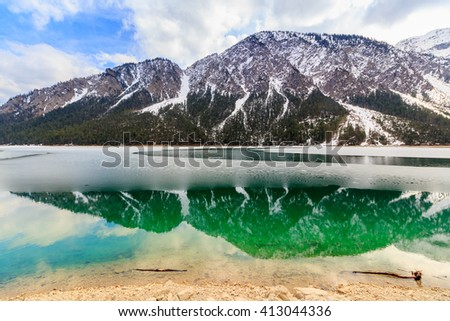 Landscape of Plansee lake and Alps mountains in winter, evening view, Tyrol, Austria.